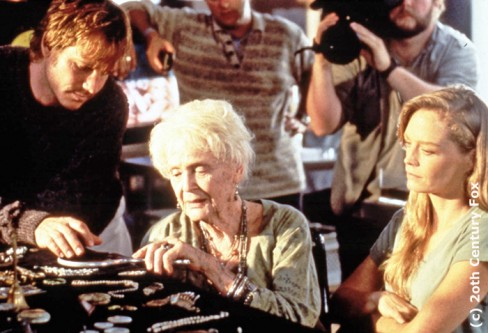 Still of Gloria Stuart with Bill Paxton and Suzy Amis on the set of Titanic, with a cameraman in the background