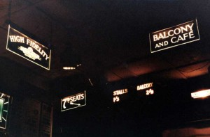 Illuminated signs in a darkened cinema foyer