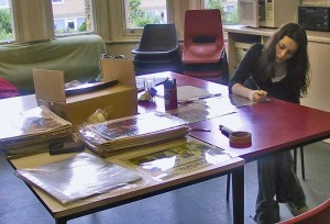 Hannah, a volunteer, seated at a table and cataloguing lobby cards