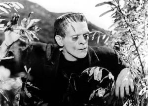 Boris Karloff as Frankenstein's Monster coming through undergrowth