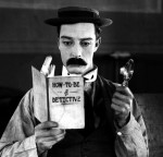 Buster Keaton with book and magnifying glass