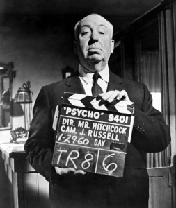 Alfred Hitchcock holding a clapperboard labelled 'Psycho'